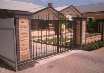 contemporary-design-double-driveway-steel-gates-mounted-between-two-pillars-and-a-complimentary-stone-and-brick-tudor-style-fence