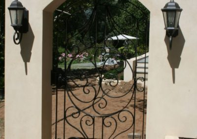 spanish-style-wrought-iron-gate-built-into-arched-fence