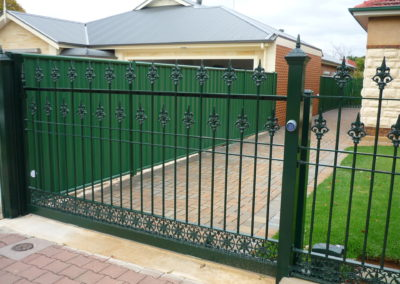 Automated electric, slide opening  single driveway gate painted heritage green