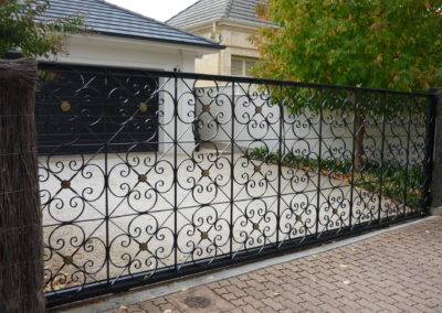 Automated electric, slide opening  single driveway gate, highly decorative panels painted black.