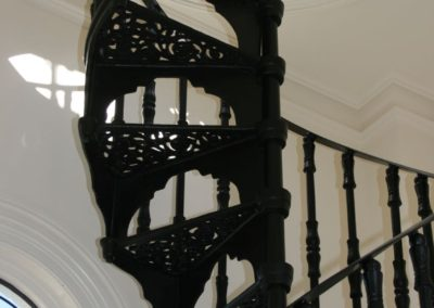 a-halfway-up-view-of-a-spiral-staircase-installed-with-an-ornate-with-lights-window-installed-in-the-stairwell