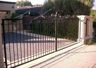 contemporary-design-automated-inwardly-opening-dual-driveway-steel-gates-painted-black-and-mounted-between-two-pillars