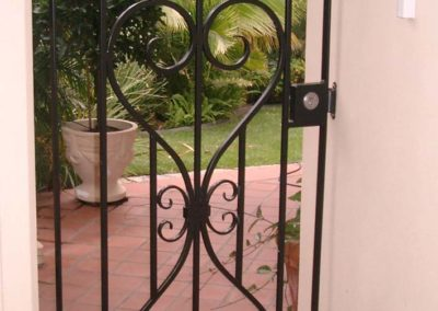 ornate-victorian-design-black-painted-lockable-gate-mounted-on-the-side-of-a-house