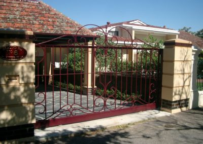 ornate-victorian-design-burgundy-painted-double-driveway-gates-in-heritage-listed-fence