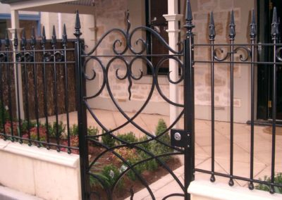 ornate-lockable-modern-design-black-front-gate-and-fence-featuring-traditional-spears-mounted-above-low-plaster-fence
